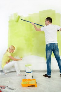 Young couple together painting wall in their flat